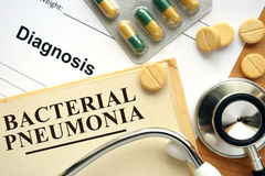 Bacterial pneumonia. Word Bacterial pneumonia on a book and pills on the wooden table royalty free stock photos