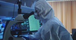 Bacterias de examen del cient?fico con el microscopio imagen de archivo
