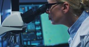 Bacterias de examen del cient?fico con el microscopio fotografía de archivo libre de regalías