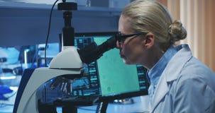Bacterias de examen del cient?fico con el microscopio almacen de video