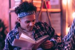 Baczna chłopiec opiera troszkę i wprawiać w zakłopotanie czytać niektóre informację w końcówce książka obraz stock
