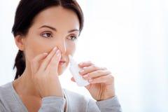 Baczna kobieta używa specjalne nosowe krople zdjęcia stock