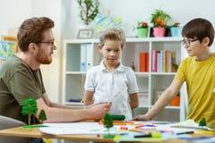 Baczne chłopiec słucha ich mądrze nauczyciel podczas lekcji obraz royalty free