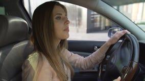 Baczny żeński kierowca opuszcza benzynową stację i patrzeje w rearview lustrach zdjęcie wideo