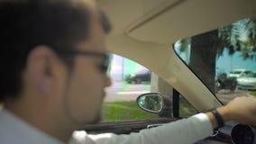 Baczny biznesmen kontroluje luksusowego samochód, szybki jeżdżenie przez miasta zdjęcie wideo