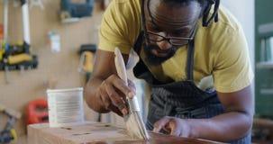 Baczny cieśla maluje drewnianą deskę 4k zbiory