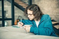 Baczny długowłosy facet z długie włosy przepisywanie notatkami w albumu obrazy stock