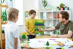 Baczny imbirowy nauczyciel wskazuje na elemencie na kształcącym plakacie zdjęcie stock