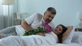 Baczny mężczyzna budzi się up żony z bukietem kwiaty, romantyczna związek opieka zbiory
