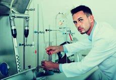 Baczny mężczyzna robi testom w wina manufactory laboratorium Zdjęcia Stock