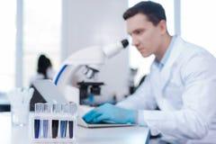Baczny męski lekarza praktykującego obsiadanie przy jego miejscem pracy Obraz Stock