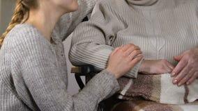 Baczny młodej damy nakrycie obezwładniał babci w wózku inwalidzkim z szkocką kratą, przytulenie zdjęcie wideo