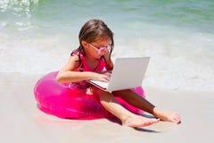 Baczny małej dziewczynki obsiadanie na plaży z laptopem Fotografia Royalty Free