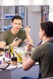 Baczny przystojny mężczyzna jest ruchliwie z makeup produktami zdjęcia royalty free