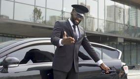 Baczny taksówkarz grzecznie otwiera samochodowego drzwi, zapraszający klient siedzieć puszek zdjęcie wideo