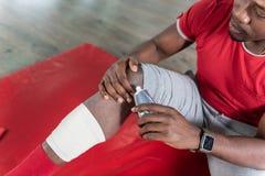 Baczny wzburzony młody człowiek rozdaje z urazem podczas sportive szkolenia obraz stock