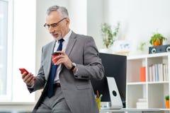 Baczny zrelaksowany facet pije świeżą kawę w biurowym stroju obraz royalty free