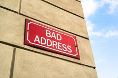Bad Address. Signboard on the wall of house - street in problematic neigborhood and residential location. City, towns, urbanic destination and negativity Stock Images
