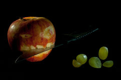 Bad apple. Apple with bad face and knife on black background. Cut grapes in the foreground Royalty Free Stock Images