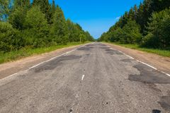 Bad asphalt road in summer in Russia. Tver region. Russia royalty free stock photography