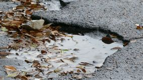 Bad asphalt tarmac rain pits in pool of floating stock footage