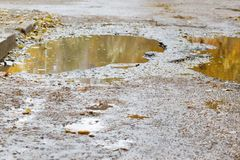 The bad asphalted road with a big pothole filled with water. Dangerous destroyed roadbed. Mirror reflections of autumn trees. The bad asphalted road with a big royalty free stock photos