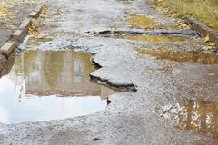 The bad asphalted road with a big potholes filled with water. Dangerous destroyed roadbed stock photo