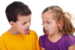 Bad behavior. Kids with bad behavior - mocking each other with tongues sticking out, closeup Stock Images