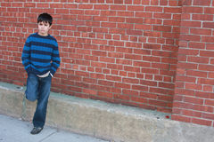 Bad Boy. Young boy with a serious scowl. Mad, mean, angry, unhappy, pissed off on the street, leaning nonchalantly against brick building with hands in pockets Royalty Free Stock Image