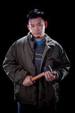 Bad boy guy holding hammer. In hand with dark background royalty free stock photography