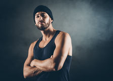 Bad boy posing. Cool bad boy with strong attitude posing arms crossed royalty free stock photography