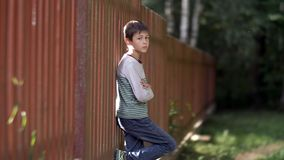 Bad boy stands near a wooden fence and looks into the camera, anger in the boy`s eyes, village, nature. Have fun stock photos