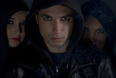 Bad boys with hood in the night. Bad boys concept,street people in darkness .Young man the head of the band in front of two woman with smoke around them,check stock image
