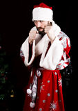 Bad brutal Santa Claus clenched his fists, ready to fight on the background of Christmas tree.  stock photography