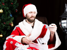 Bad brutal Santa Claus discontentedly reads letter with the wishes, on the background of Christmas tree.  stock image