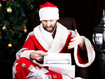 Bad brutal Santa Claus discontentedly reads letter with the wishes, on the background of Christmas tree.  stock photography