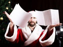 Bad brutal Santa Claus discontentedly reads letter with the wishes and throwing paper, on the background of Christmas. Bad brutal Santa Claus discontentedly stock photos