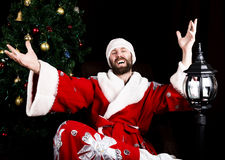 Bad brutal Santa Claus smiles and spread his hands in different side on the background of Christmas tree royalty free stock images