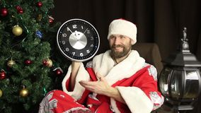 Bad brutal Santa Claus smiling and shows the clock, five minutes to twelve, on the background of Christmas tree stock video