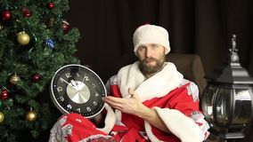 Bad brutal Santa Claus smiling and shows the clock, five minutes to twelve, on the background of Christmas tree stock footage
