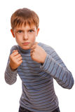 Bad bully child boy blond angry aggressive fights. In striped shirt isolated on white background royalty free stock photography