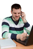 Bad Business. Man trying to smash his notebook fith his fist while talking on mobile phone Royalty Free Stock Images