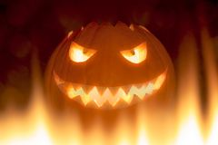 Bad carved halloween pumpkin in hot burning hell fire flames. The big helloween pumpkin has a mad face with glowing eyes and also a glow in its mouth and teeth Stock Photos