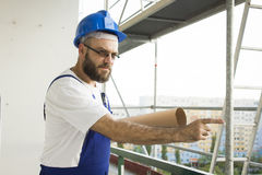 Bad Construction worker in working outfit and in helmet stands at a high altitude on a construction site with plans Stock Photo