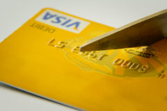 Bad credit. Concept for bad or damaged credit - Scissors cutting a yellow debit/credit card Royalty Free Stock Photos