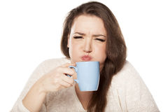Bad cup of tea. Young woman is squeamish from her tea stock photos