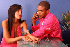 Bad Date. African American couple in a martini bar.Man talking on cell phone while the woman sits by annoyed and bored suffering from the Cell Phone Blues Royalty Free Stock Image