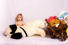 Bad day. Baby and her toy dog transporting clothes in a wood troley, studio shot Royalty Free Stock Photography