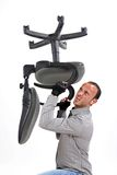 Bad day in office. Angry bussinesman holding a chair Stock Image