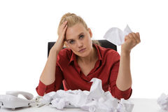 Bad day. Office worker with screwed up paper ball on her desk not looking to happy Stock Images